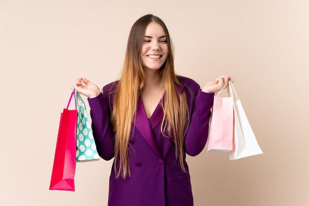 Młoda caucasian kobieta na beżowej ściany mienia torba na zakupy i zaskakująca