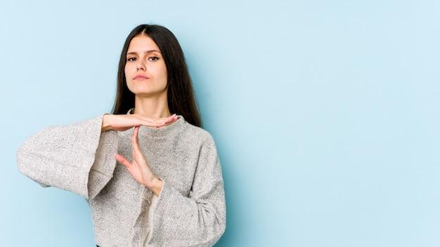 Młoda caucasian kobieta na błękit ścianie pokazuje timeout gest.