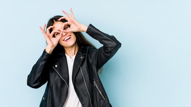 Młoda caucasian kobieta na błękit ściany seansu ok podpisuje oczy