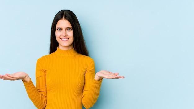 Młoda caucasian kobieta na błękitnej ścianie robi skala z rękami, czuje się szczęśliwy i pewny siebie.