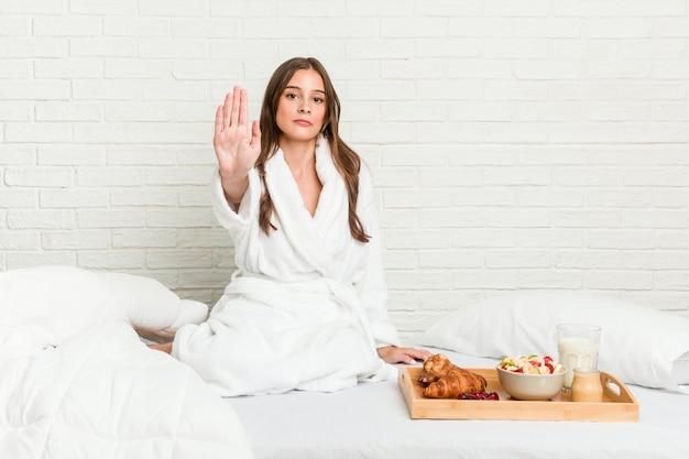 Młoda caucasian kobieta na łóżkowej pozyci z szeroko rozpościerać ręką pokazuje przerwa znaka, zapobiegający ciebie.