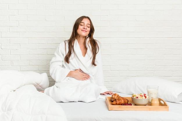 Młoda caucasian kobieta na łóżku dotyka brzucha, uśmiecha się delikatnie, jedzenia i satysfakcji pojęcie.