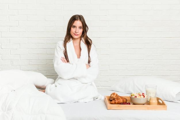 Młoda caucasian kobieta na łóżku marszczy brwi z niezadowolenia, trzyma założone ręce.