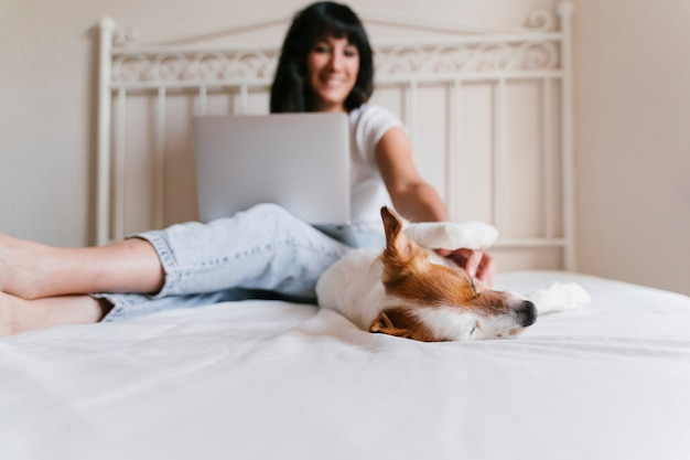 Młoda caucasian kobieta na łóżku pracuje na laptopie. poza tym ładny mały pies. miłość do zwierząt i koncepcja technologii. styl życia w pomieszczeniu