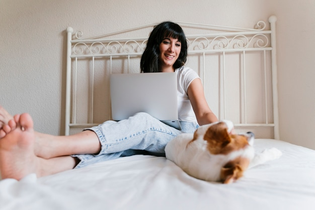 Młoda caucasian kobieta na łóżku pracuje na laptopie. poza tym ładny mały pies.