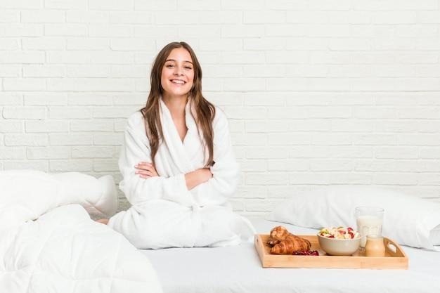 Młoda caucasian kobieta na łóżku śmia się i ma zabawę.