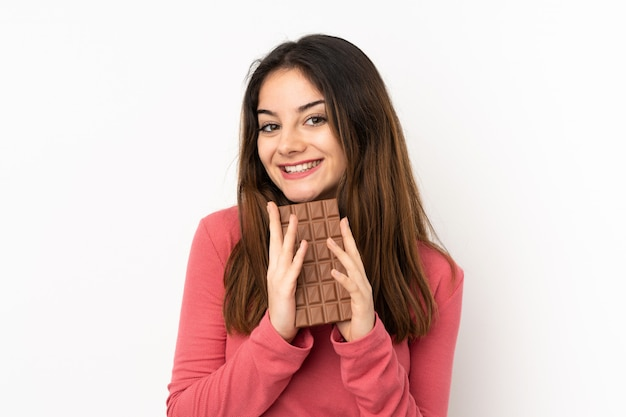 Młoda caucasian kobieta na menchii ścianie bierze czekoladową pastylkę i szczęśliwa