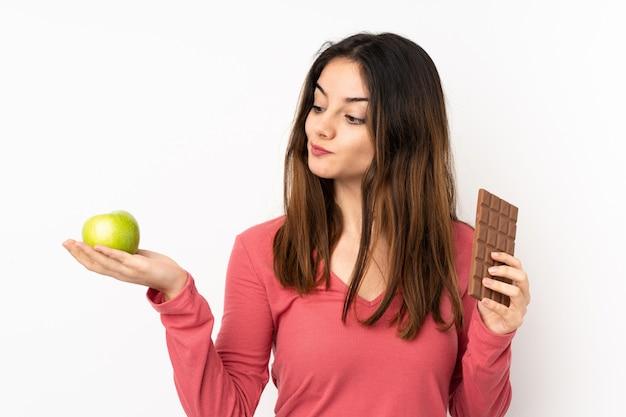 Młoda caucasian kobieta na menchii ścianie ma wątpliwości podczas gdy brać czekoladową pastylkę w jednej ręce i jabłko w drugiej