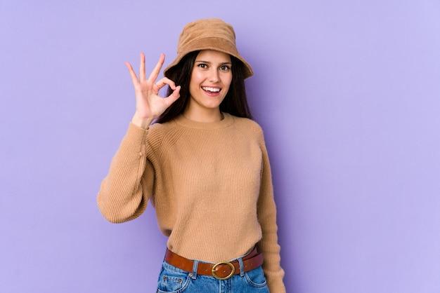 Młoda caucasian kobieta na purpurach izoluje rozochoconego i ufnego seansu ok gest.