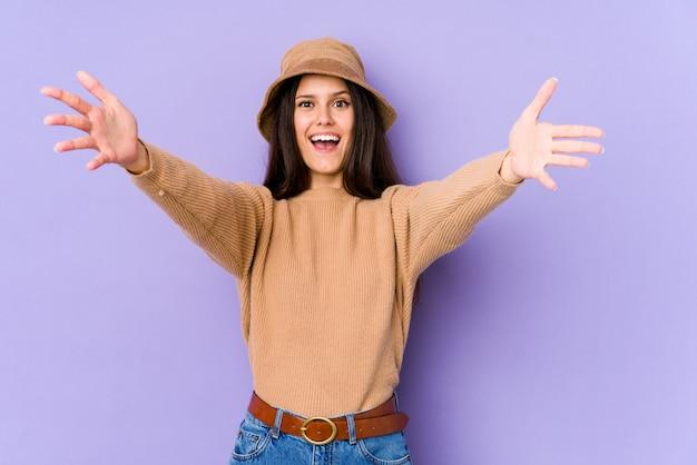 Młoda caucasian kobieta na purpurowej ścianie czuje się pewnie, ściskając