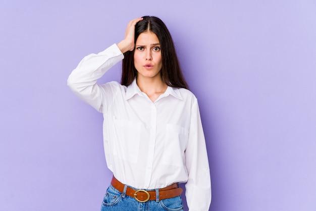Młoda caucasian kobieta na purpurowej ścianie jest zszokowana, przypomniała sobie ważne spotkanie.