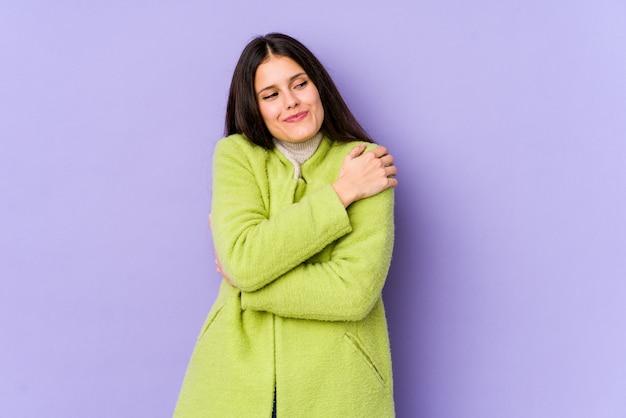 Młoda caucasian kobieta na purpurowych ścianach ściska, ono uśmiecha się beztroski i szczęśliwy.