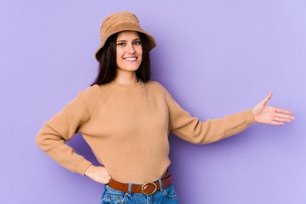 Młoda caucasian kobieta na purpury ścianie pokazuje mile widziany wyrażenie.