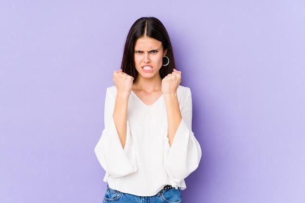 Młoda caucasian kobieta na purpury ścianie pokazuje pięść
