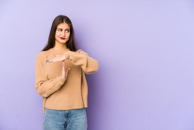 Młoda caucasian kobieta na purpury ścianie pokazuje timeout gest.
