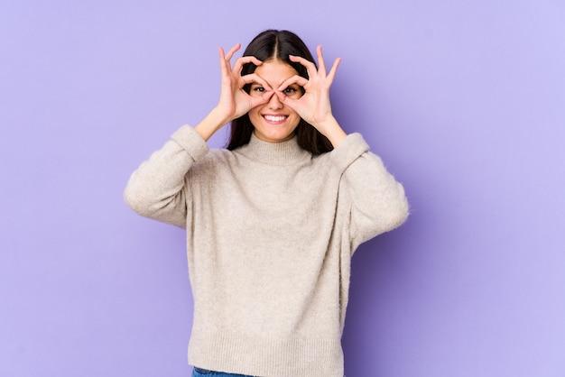 Młoda caucasian kobieta na purpury ściany seansu ok podpisuje oczy