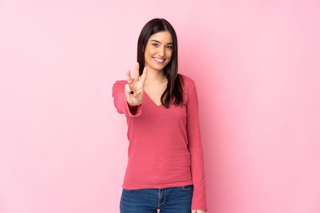 Młoda caucasian kobieta nad ścianą szczęśliwą i liczy trzy z palcami