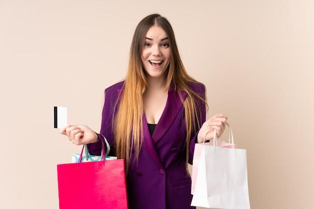 Młoda caucasian kobieta odizolowywająca na beżowej ściany mienia torba na zakupy i zaskakująca