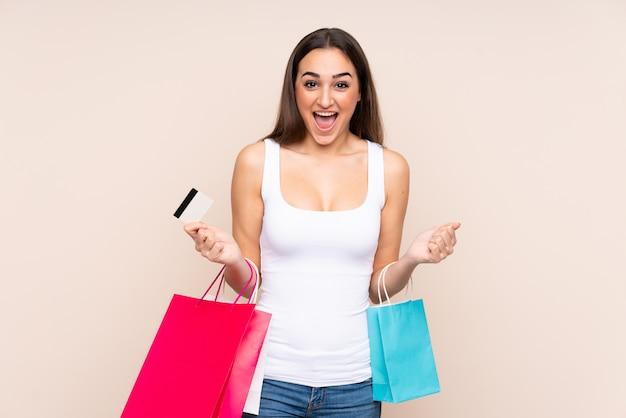 Młoda caucasian kobieta odizolowywająca na beżowych mień torba na zakupy i zaskakująca