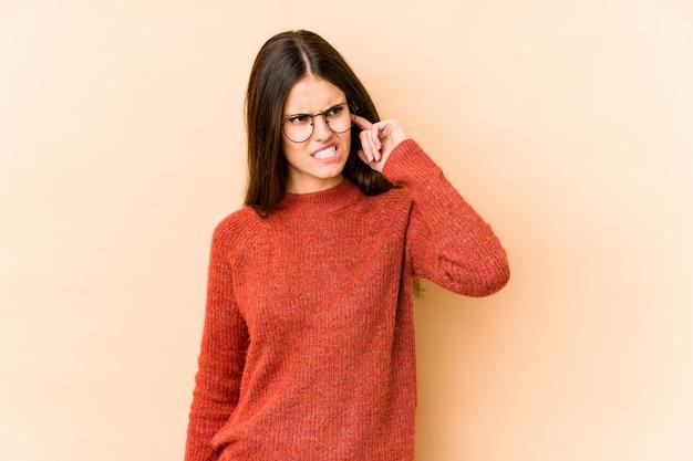 Młoda caucasian kobieta odizolowywająca na beżu ściennych nakrywkowych ucho z rękami.