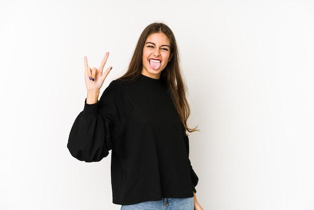 Młoda caucasian kobieta odizolowywająca na bielu pokazuje rogu gest jako rewoluci pojęcie.