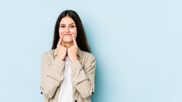 Młoda caucasian kobieta odizolowywająca na błękit ścianie wątpi między dwiema opcjami.