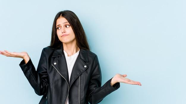 Młoda caucasian kobieta odizolowywająca na błękit ścianie wprawiać w zakłopotanie i wątpliwie wzrusza ramionami ramiona trzymać odbitkową przestrzeń.