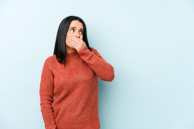 Młoda caucasian kobieta odizolowywająca na błękitnym tle rozważna patrzejący odbitkowej przestrzeni nakrywkowy usta z ręką.