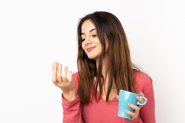 Młoda caucasian kobieta odizolowywająca na menchiach trzyma kolorowych francuskich macarons i filiżankę mleka