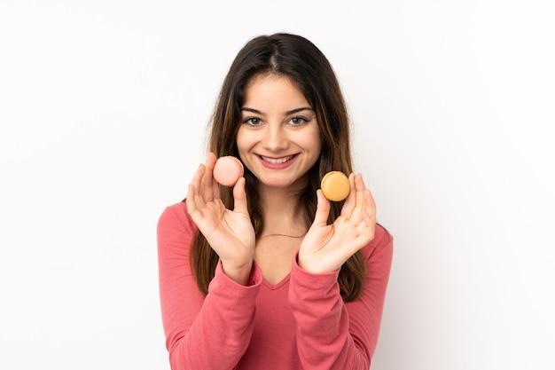 Młoda caucasian kobieta odizolowywająca na menchii ścianie oferuje kolorowych francuskich macarons