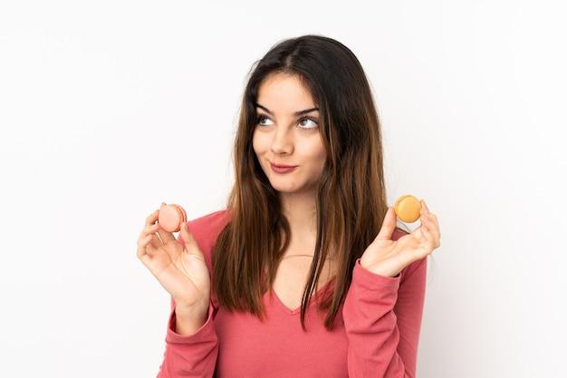 Młoda caucasian kobieta odizolowywająca na menchii ścianie trzyma kolorowych francuskich macarons i główkowanie
