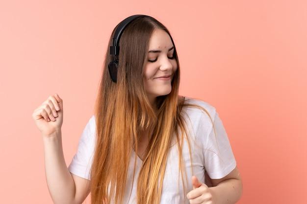 Młoda caucasian kobieta odizolowywająca na menchii ściany słuchającej muzyce i tanu