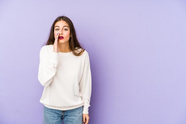 Młoda caucasian kobieta odizolowywająca na purpurach mówi tajną gorącą hamującą wiadomość i patrzeje na boku