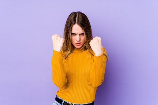 Młoda caucasian kobieta odizolowywająca na purpurach pokazuje pięść, agresywny wyraz twarzy.