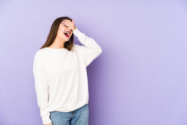 Młoda caucasian kobieta odizolowywająca na purpurach śmia się z radością utrzymując ręce na głowie. koncepcja szczęścia.