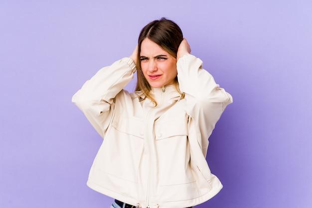 Młoda caucasian kobieta odizolowywająca na purpurowych nakrywkowych ucho z rękami.
