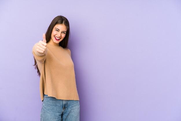 Młoda caucasian kobieta odizolowywająca na purpurowym ono uśmiecha się i podnosi kciuku up