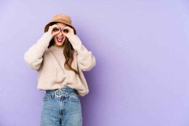 Młoda caucasian kobieta odizolowywająca na purpurowym seansu ok podpisuje oczy