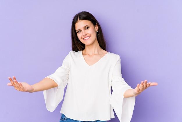 Młoda caucasian kobieta odizolowywająca na purpury ścianie pokazuje mile widziany wyrażenie.