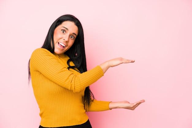 Młoda caucasian kobieta odizolowywająca na różowej ścianie zszokował i zadziwiał trzymający odbitkową przestrzeń między rękami.