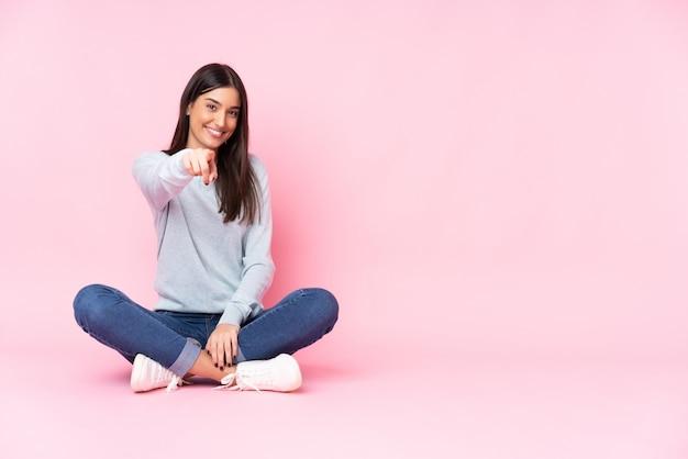 Młoda caucasian kobieta odizolowywająca na różowych ściana punktach dotyka ciebie z ufnym wyrażeniem