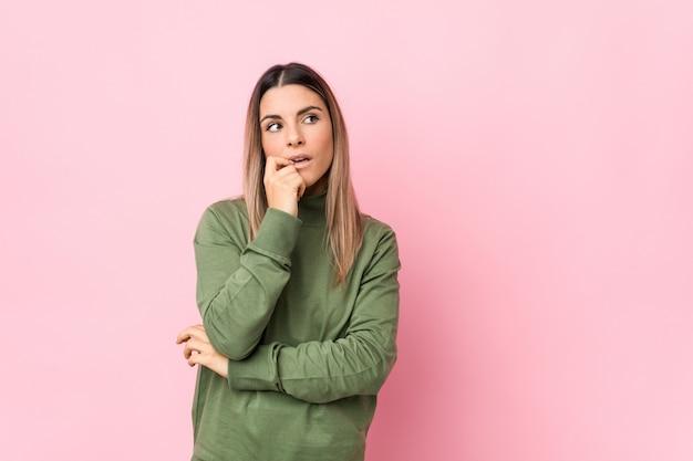 Młoda caucasian kobieta odizolowywał zrelaksowanego główkowanie o coś patrzeje odbitkową przestrzeń.