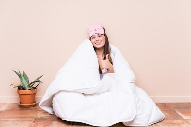 Młoda caucasian kobieta odpoczywa z kołderką uśmiecha się kciuk up i podnosi