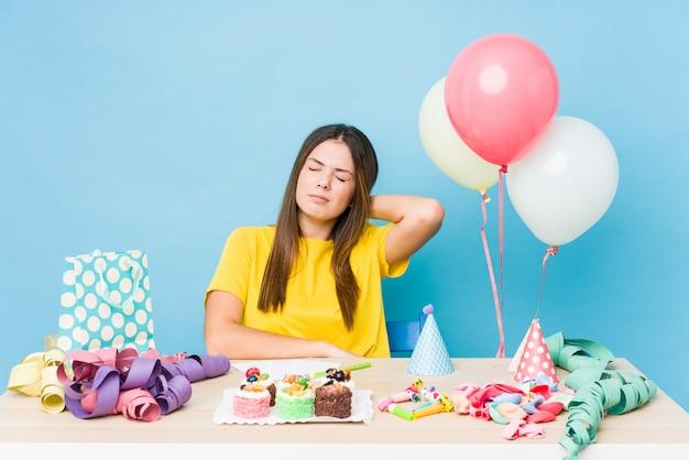 Młoda caucasian kobieta organizuje urodziny cierpi ból szyi z powodu siedzącego trybu życia.