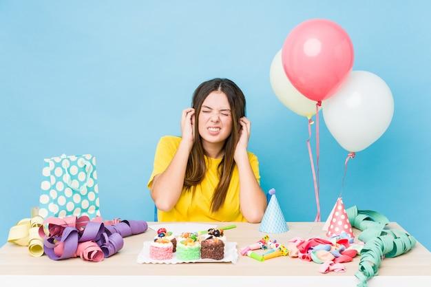 Młoda caucasian kobieta organizuje urodziny zakrywa ucho z rękami.