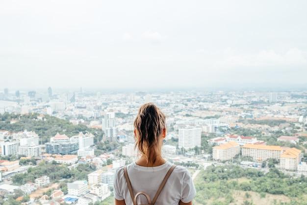 Młoda caucasian kobieta patrzeje miasto z wysokości