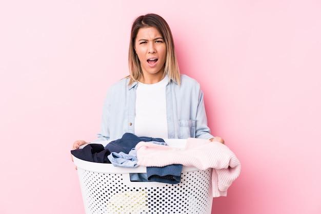 Młoda caucasian kobieta podnosi brudne ubrania krzyczy bardzo gniewny i agresywny.