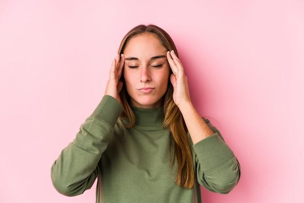 Młoda caucasian kobieta pozuje odosobnione wzruszające świątynie i ma migrenę.