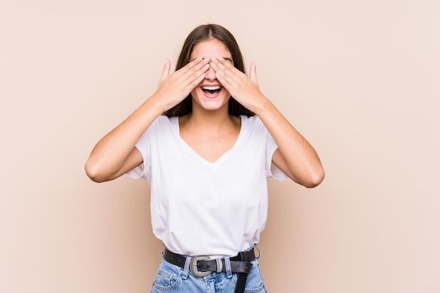 Młoda caucasian kobieta pozuje odosobnionego zakrywa oczy rękami, uśmiecha się szeroko czekający na niespodziankę.