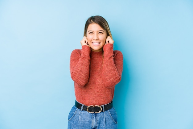 Młoda caucasian kobieta pozuje odosobnionych nakrywkowych ucho z rękami.
